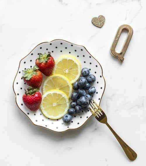 strawberry, lemon, and berries on a plate